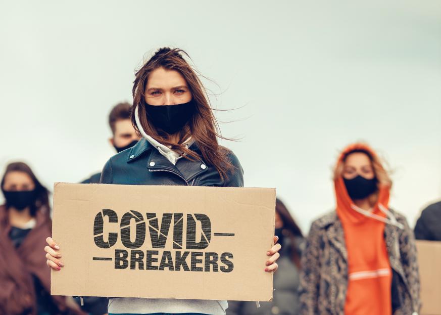 "jeunes covid breakers masqués tenant une affiche ""covid breakers'"