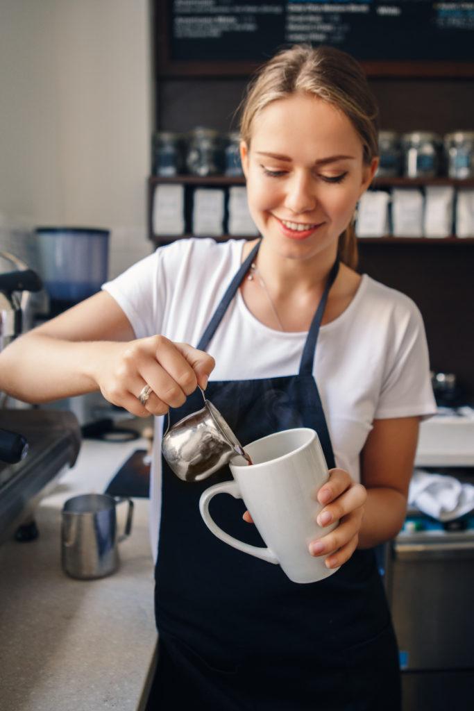 Jeune serveuse versant du café dans une tasse