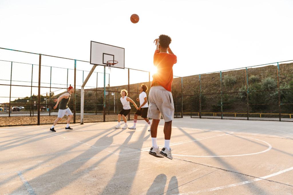 Basketteur covid breaker lançant un ballon de basket vers un panier défendu par d'autres basketteurs sur un terrain de basket