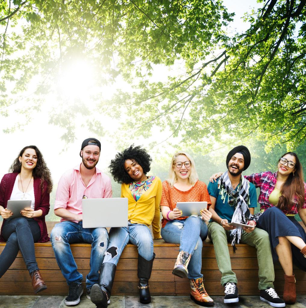 Jeunes covid breakers souriant assis en groupe sur un banc dans un parc