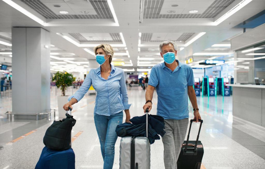 Dankzij hun Covid-certificaat kunnen twee mensen met mondmasker reizen. Ze zijn in een luchthaven en trekken hun koffers voort.