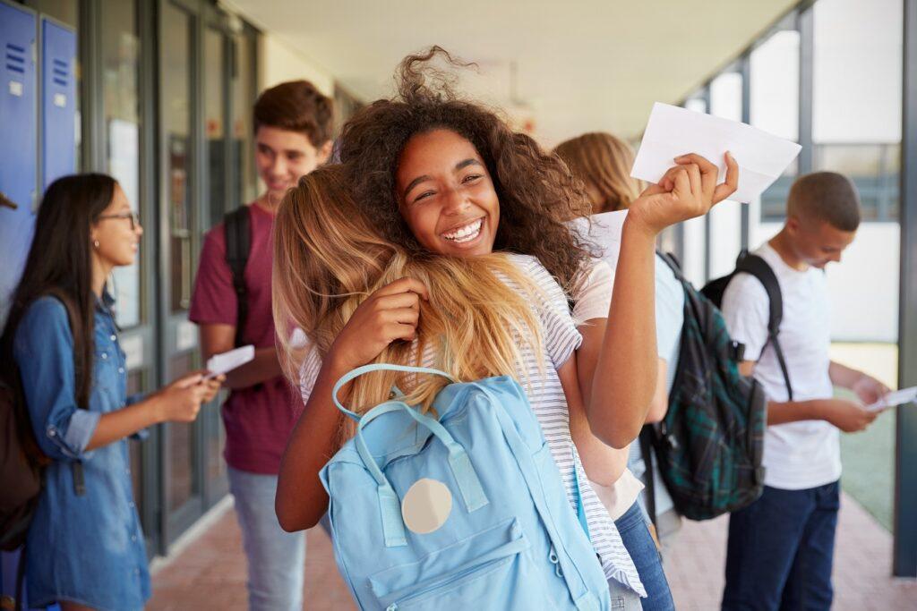 twee studenten omhelzen elkaar in de gangen van hun school, blij om weer samen te zijn na de covid