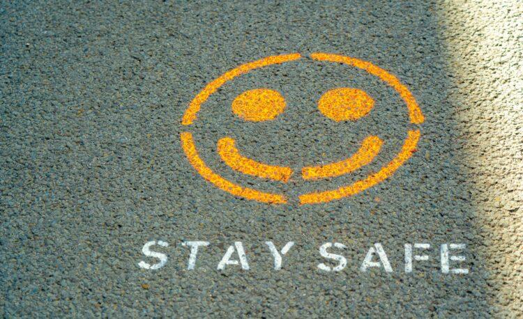 """emoticon van een lachende man op een stoep """"blijf veilig"""" voor de covid"""